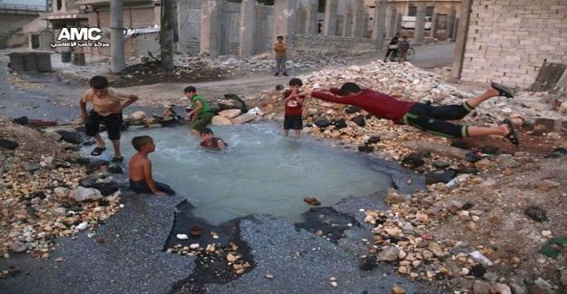 Bir Bomba Sonucu Açılan Çukurdan Kendilerine Havuz Yapan Çocuklar