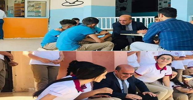 Okul merdivenlerinde bir Adam oturmuş, etrafında da öğrenciler! Konuşmayan, dinleyen bir adam.